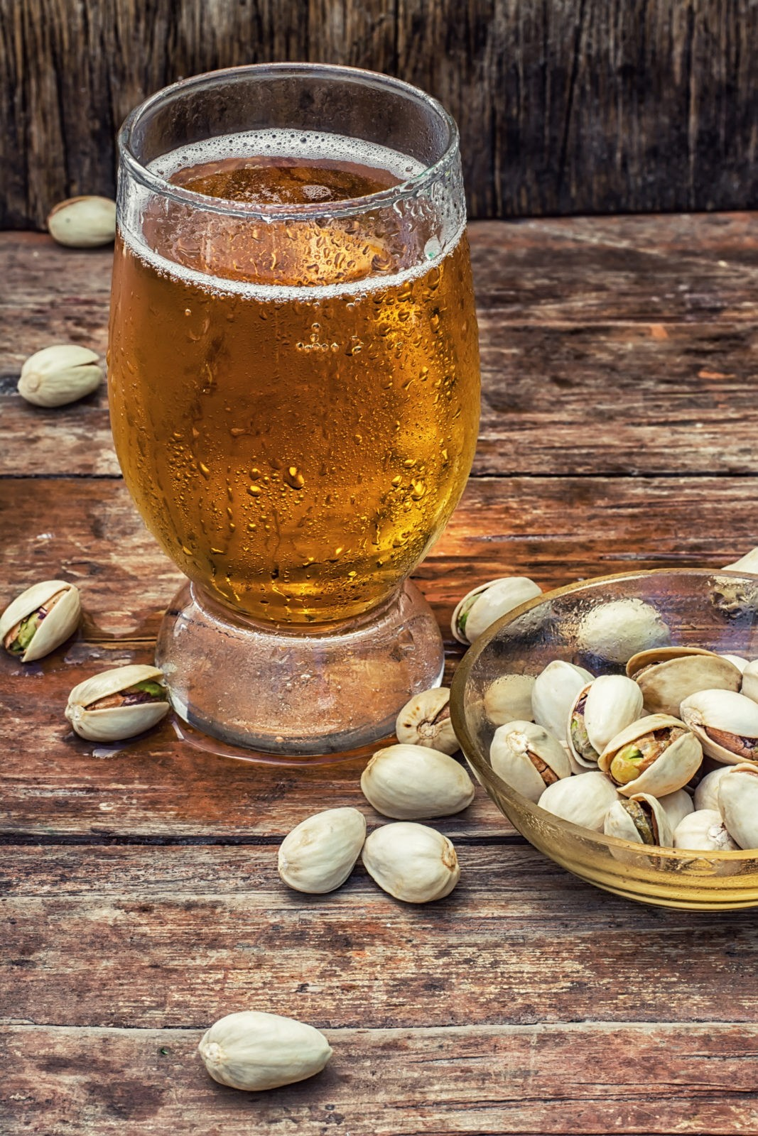 beer light beer on wooden table with saucer of salted pistachios.Photo tinted.Selective focus
