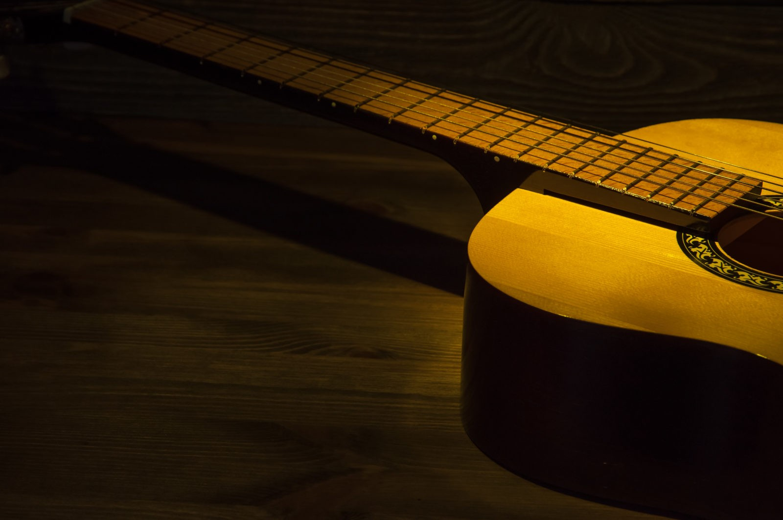 Acoustic guitar on a wooden table lit by a ray of light. Side view.